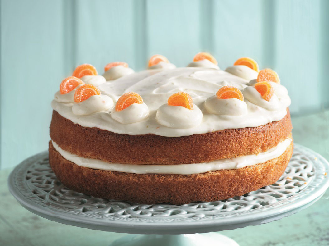 Fresh Orange Cake from recipe booklet, on a cake stand against a blue wall