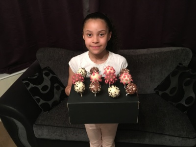 Aliza holding a tray of cake pops