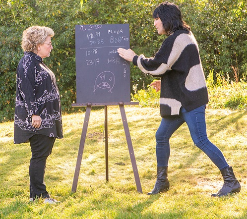 Great Stand Up To Cancer Bake Off hosts Sandi and Noel by a blackboard