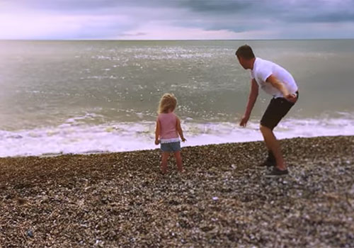 Brett throwing stones into the sea with his daughter.