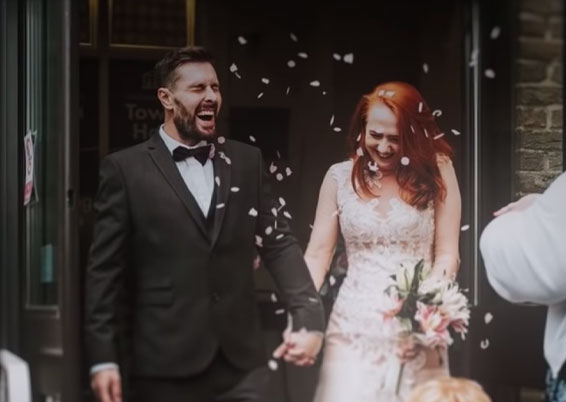 Dan and his wife Becca on their wedding day, laughing as confetti is thrown at them