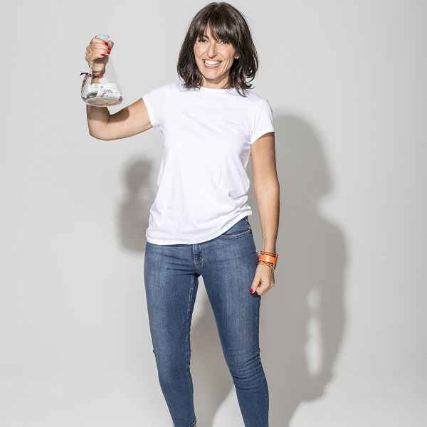 Davina McCall with a conical flask full of cash
