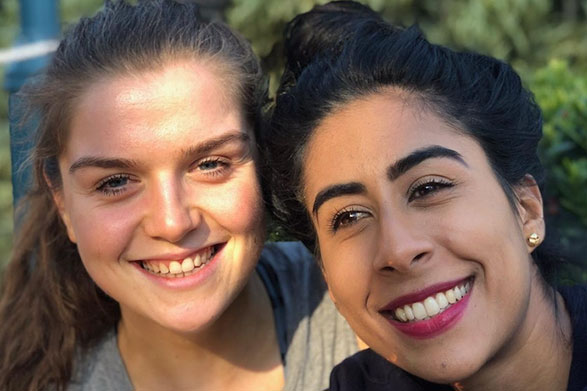 Emily Hayward and her wife Aisha smiling outside in the sun.