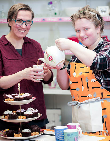Thirza and Hendrikje pouring tea surrounded by their bake sale food