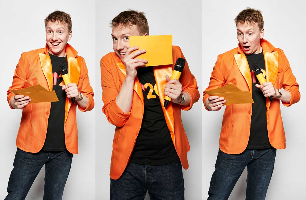 Joe Lycett holding a microphone and quiz cards in a orange jacket, smiling and laughing