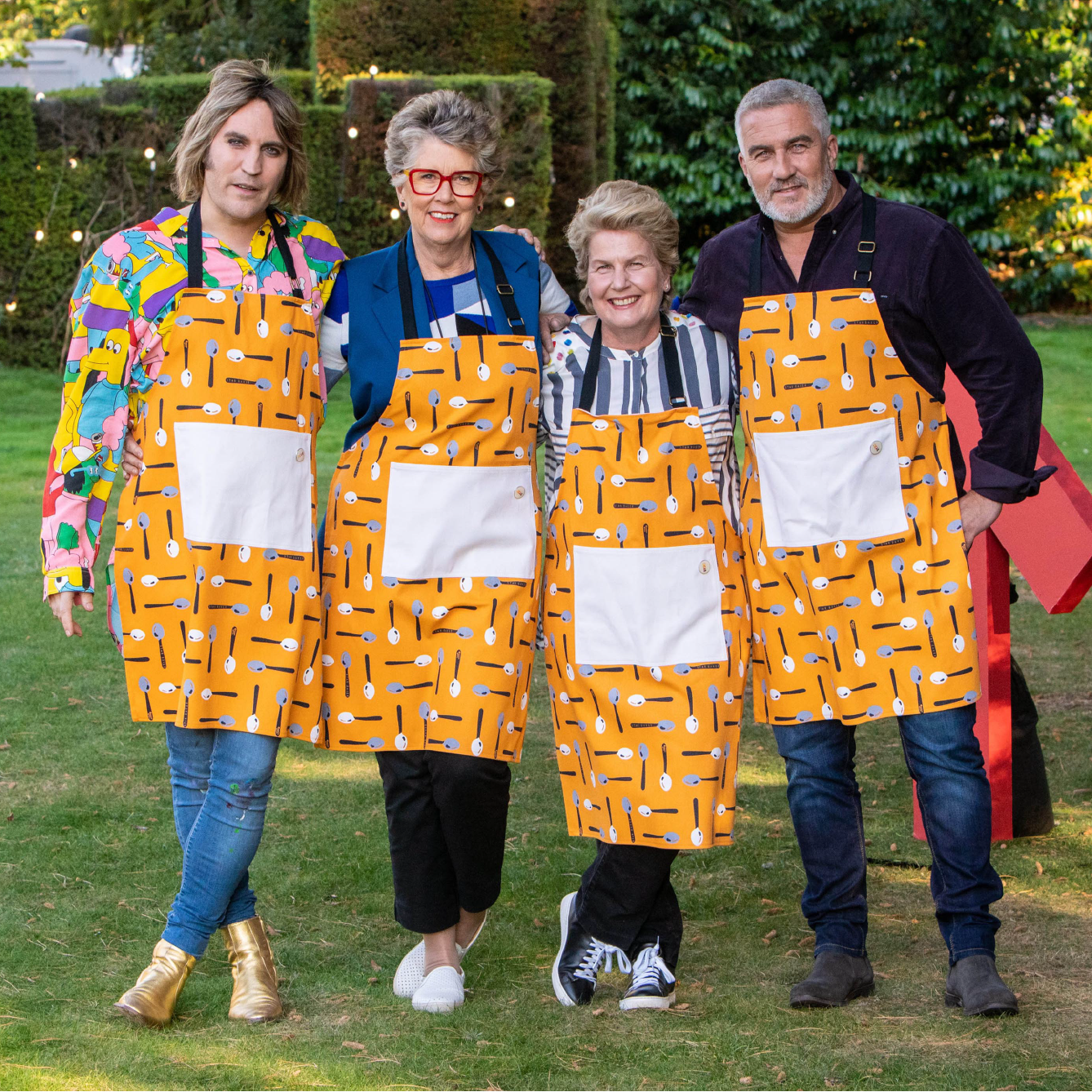 Four judges wearing Star Baker apron, in garden.