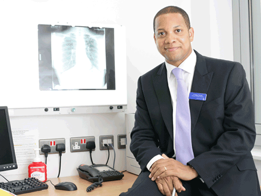 Professor Dean Fennell sitting by a lung X-ray