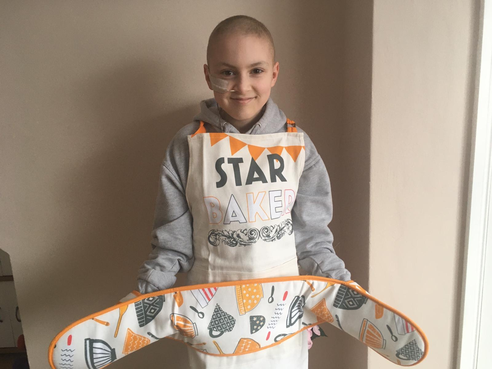 Rebecca in The Great Stand Up To Cancer Bake Off Apron and Oven Gloves smiling at the camera.