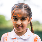 A school girl with paint orange paint on her face