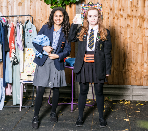 Two girls running fundraising stall at school