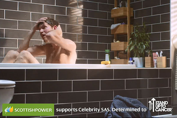 A man in a bath tub with the words 'Scottish Power supports celebrity SAS. Determined to Stand Up To Cancer.