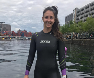 Janey wearing wet suit in front of river
