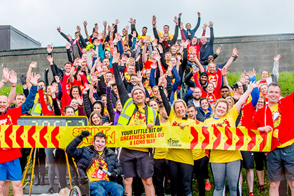 A group of Sprintathon fundraisers cheering and holding a banner