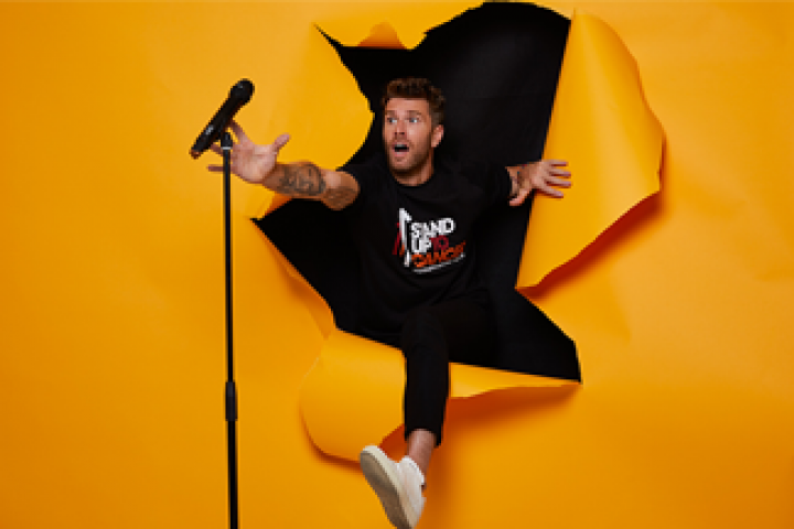 Comedian Joel Dommett breaking through an orange screen to reach his microphone