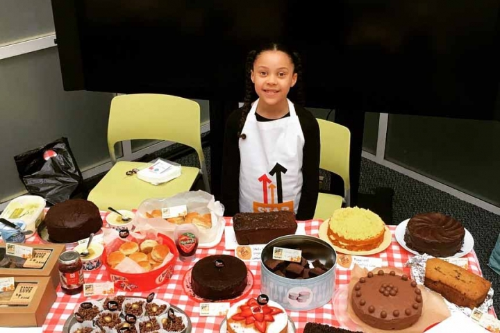 Aliza standing in front of a table of cakes for her Stand Up To Cancer baking event