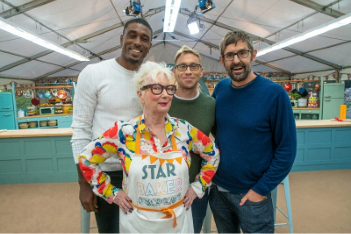 Jenny Eclair in a Star Baker Apron, with Ovie Soko, Louis Theroux and Russell Howard stood behind her