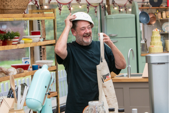 Johnny Vegas with tin on his head and holding apron.