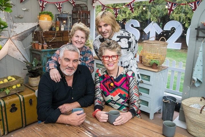 Great British Bake Off judges and hosts sitting at the table for Stand Up To Cancer