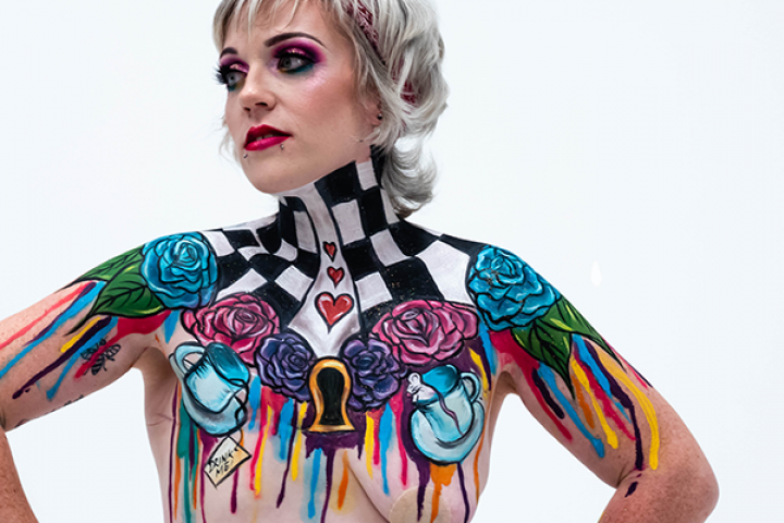 A woman with a single mastectomy facing the camera, showing a vivid body art design