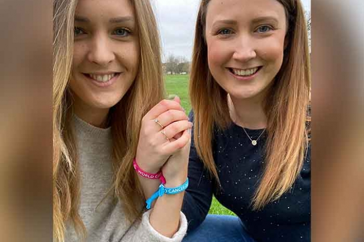 The secondary sisters, Laura and Nicky, holding hands and showing their World Cancer Day Unity Bands