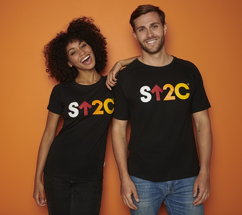A man and a woman wearing Stand Up To Cancer merchandise