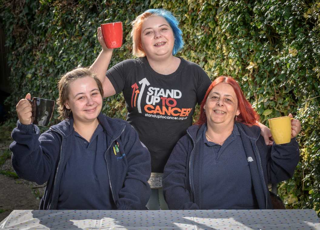 Laura and her family in Stand Up To Cancer t-shirts holding mugs