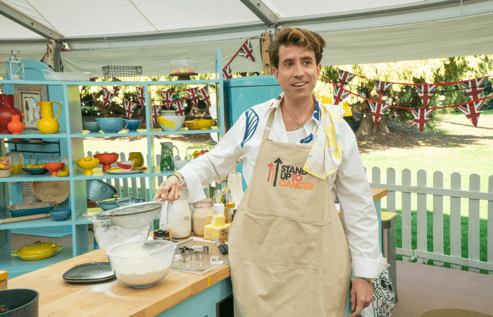 Nick Grimshaw holding a sieve in the Bake Off tent